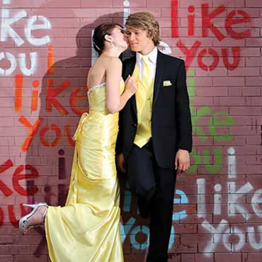 prom couple in front of brick wall with graffiti